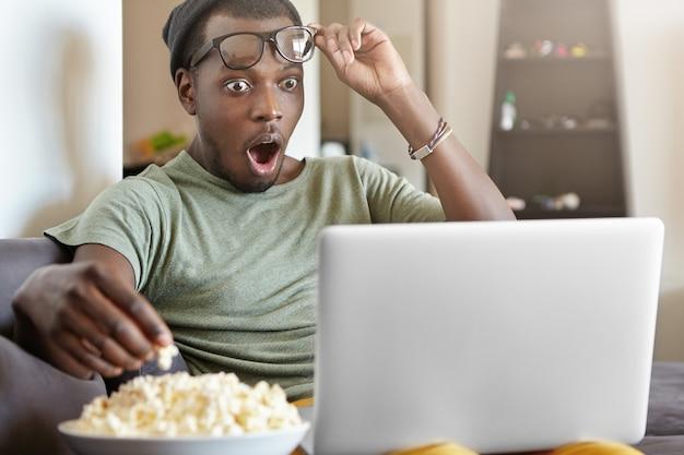 Betäubter junger mann, der vor erstaunen seine brille abnimmt, während er detektivserien online auf einem laptop sieht