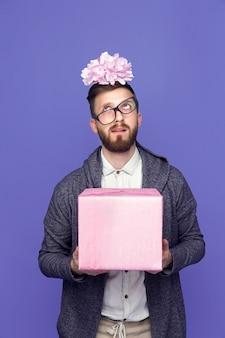 Betäubter mann mit rosa eingewickeltem geschenk