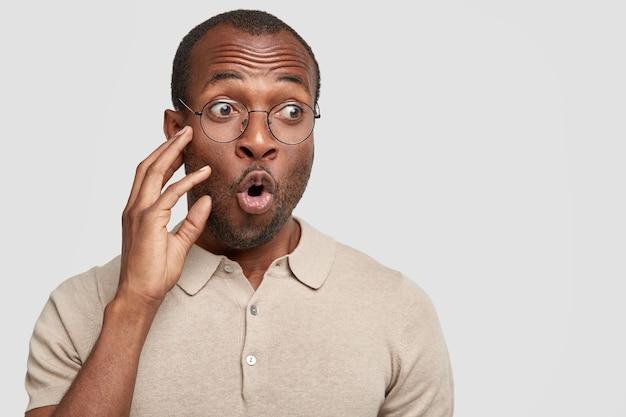 Betäubter mann mit überraschtem gesichtsausdruck, wundert sich über die neuesten nachrichten, hat einen schockierten blick, trägt ein beiges t-shirt und steht an der weißen wand