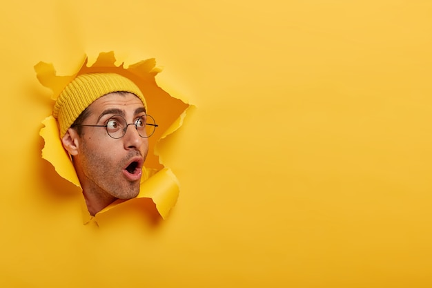 Betäubter mann schaut mit großer überraschung oder angst beiseite, öffnet den mund weit, trägt hut und runde brille
