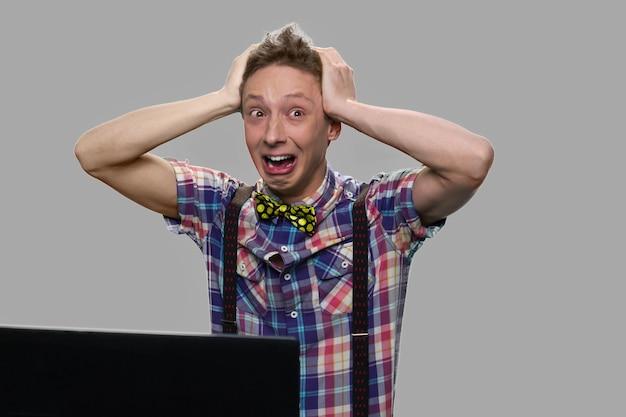 Betäubter schockierter jugendlich junge auf grauem hintergrund. emotionaler teenager, der hände auf kopf hält, während er gegenüber laptop sitzt.