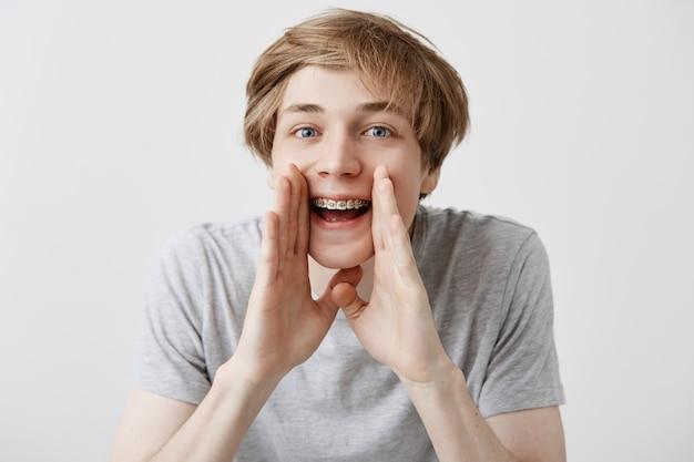 Betäubter überglücklicher kaukasischer männlicher student schreit vor aufregung, hält die hände in der nähe des mundes und freut sich, die universität oder das college zu betreten. emotional glücklich überrascht junger blonder mann schreit wow oder omg