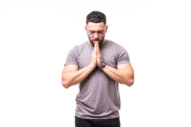 Bete für portugal. argentinischer fußballfan betet für das spiel der argentinischen nationalmannschaft auf weißem hintergrund. fußballfans konzept.