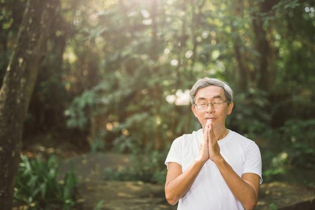 Bete von älteren asiatischen mann im naturpark