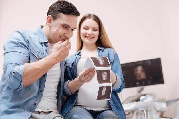 Beteiligt überwältigtes junges paar, das einen termin im sonographie-schrank hat und ultraschall-fötus-scan genießt, während es liebe ausdrückt
