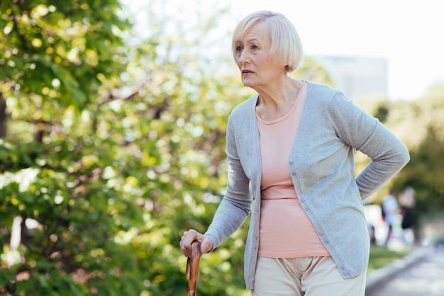 Beteiligte charmante alte frau, die ihren rücken berührt und sich auf den stock stützt, während sie im park geht