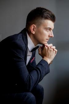 Beteiligter bräutigam, der mit seinen händen spielt und zur seite beim tragen des smokings, sitzend auf schwarzem studiohintergrund schaut