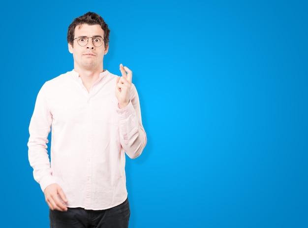 Beteiligter junger mann, der eine geste der gekreuzten finger tut