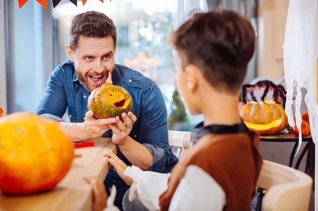 Beteiligter vater. strahlender lustiger vater, der sich vor der halloween-feier mit seinem aufgeregten sohn in streiche verwickelt fühlt
