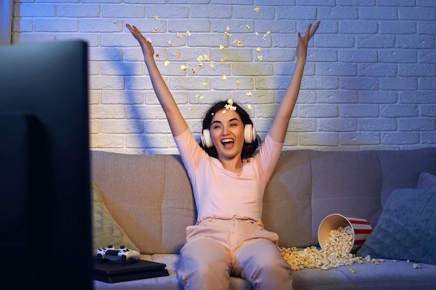 Beteiligtes spielermädchen, das kopfhörer trägt und videospiele spielt. frau feiert den sieg und wirft zu hause popcorn hoch