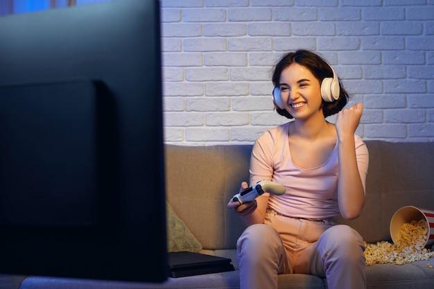 Beteiligtes spielermädchen, das kopfhörer trägt und videospiele spielt. frau feiert den sieg zu hause