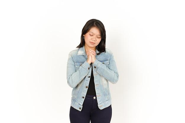 Beten geste der schönen asiatischen frau mit jeansjacke und schwarzem hemd isoliert auf weiss