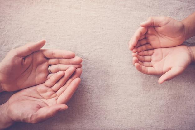 Betende hände des kindes und des erwachsenen, mitgefühlspende, nächstenliebe, helfendes handkonzept