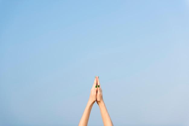 Betende hände zeigten in richtung des himmels, der yogaübung und des ausdehnens des konzeptes