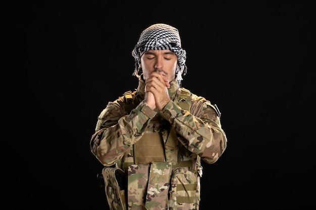 Betender männlicher soldat in tarnung an einer schwarzen wand