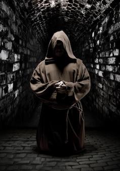 Betender mönch im dunklen tempelkorridor