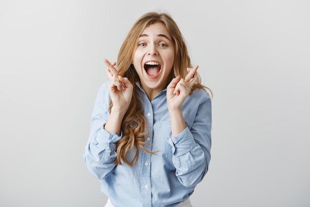 Betet, wo gehört, mädchen gewinnt den ersten platz. aufgeregte glückliche europäische frau mit blonden haaren, die gekreuzte finger heben und vor glück und überraschung schreien, froh sein, von positiven nachrichten triumphieren