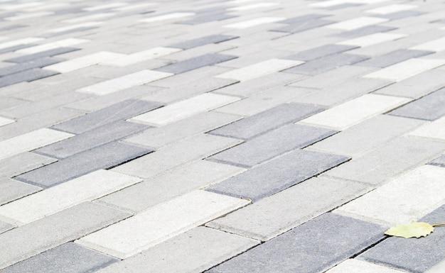 Beton oder gepflasterte neu verlegte graue pflasterplatten oder steine für fußböden oder gehwege. betonpflastersteine im hinterhof oder straßenpflaster. gartenziegelweg im hof auf sandigem untergrund.
