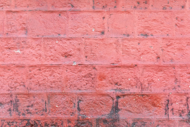 Betonblockwand gemalte rote farbe des hintergrunds und der beschaffenheit.