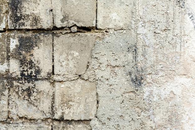Betonmauer mit herausgestellten gealterten ziegeln