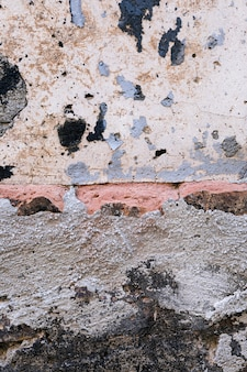 Betonmauer mit ziegelsteinen und schmutzigen flecken