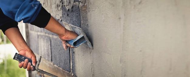 Betonputzer zum erstellen von hintergrundwänden für industriearbeiter mit putzwerkzeugen.