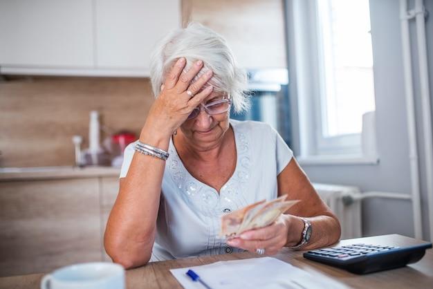 Betonte ältere frau erledigt bank- und verwaltungsarbeit zu hause