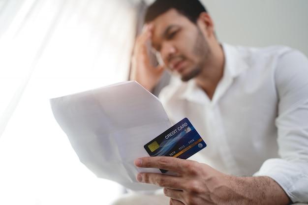 Betonte asiatischer mann, der kreditkarte und rechnung hält