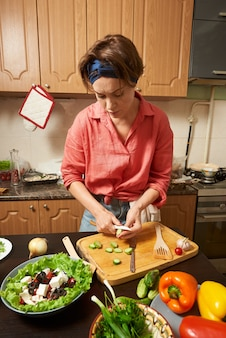 Betonte frau, die einen gesunden salat zubereitet