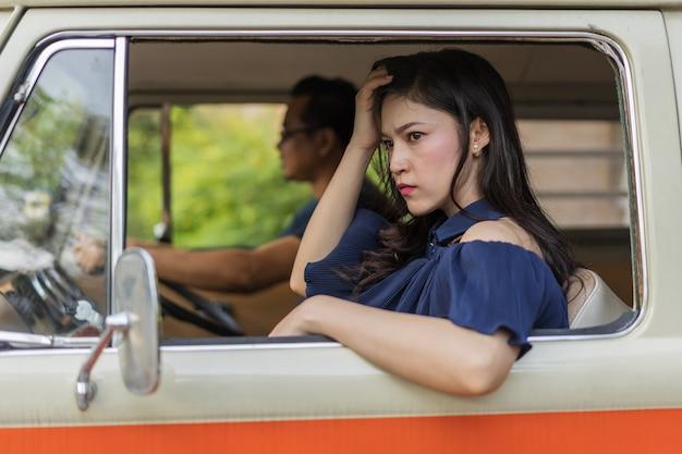 Betonte frau, die innerhalb des weinleseautos sitzt
