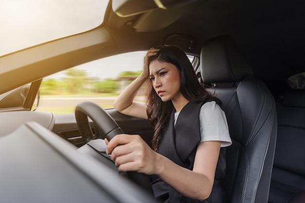 Betonte frau, die innerhalb eines autos sitzt