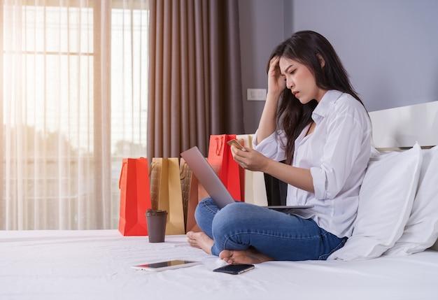 Betonte frau, die laptop für das on-line-einkaufen auf bett verwendet und problem mit blockierter kreditkarte hat