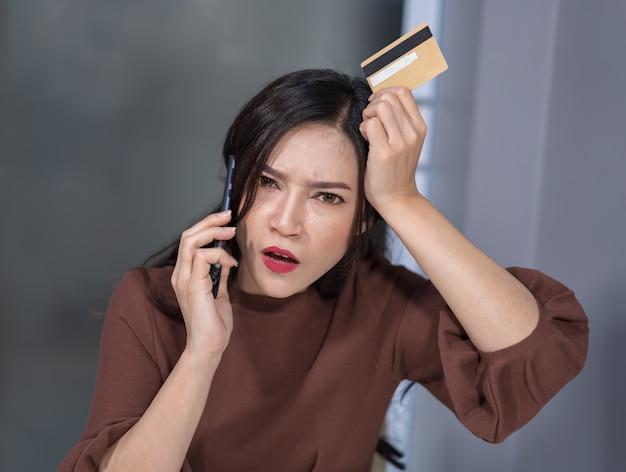 Betonte frau, die telefonisch und holdind kreditkarte zum on-line-einkaufen nennt