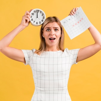 Betonte frau, die uhr und zeitraumkalender hält