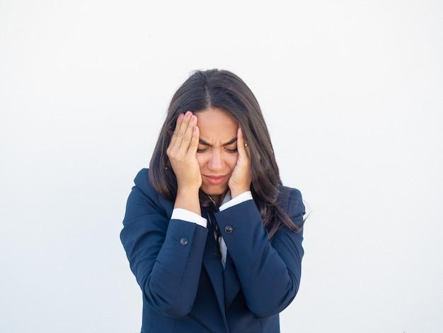 Betonte frustrierte geschäftsfrau, die unter kopfschmerzen leidet