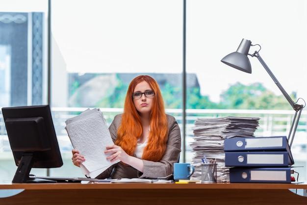 Betonte geschäftsfrau mit stapel papieren