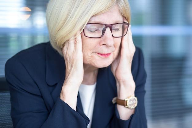 Betonte gesicht der älteren geschäftsfrau in gläser
