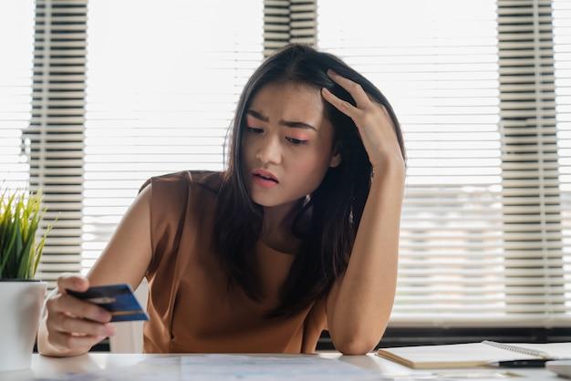 Betonte junge asiatische frau, die kreditkarte und kein geld hält, um kreditkarteschuld zu zahlen