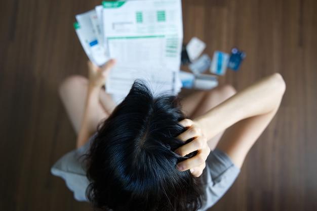 Betonte junge asiatische frau, die rechnungen hält und darüber nachdenkt, geld zu finden, um die rechnung zu bezahlen.