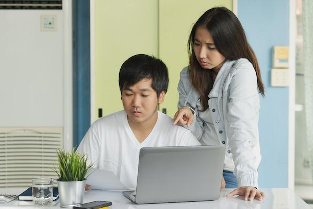 Betonte junge asiatische paare, die ausgabenmitteilung von der bank über wohnungsbaudarlehenskredit der verspäteten zahlung betrachten.