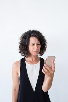 Betonte unglückliche frau mit dem smartphone, der schlechtes neues erhält