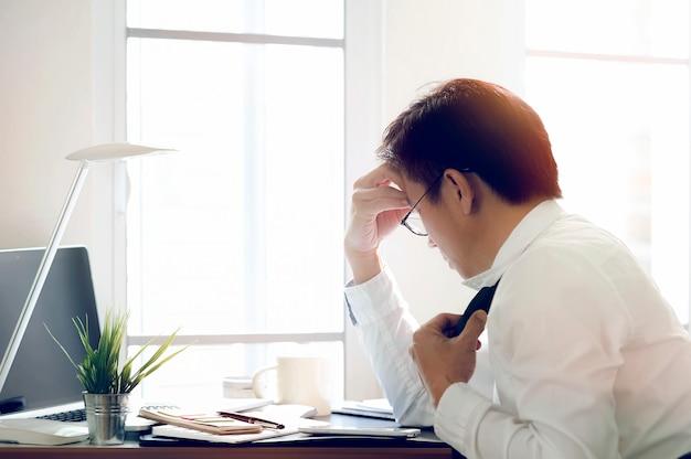 Betonter asiatischer geschäftsmann, der beim sitzen an seinem arbeitsplatz krank und müde sich fühlt