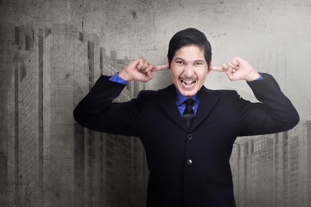 Betonter asiatischer geschäftsmann, der seine ohren mit den fingern verstopft