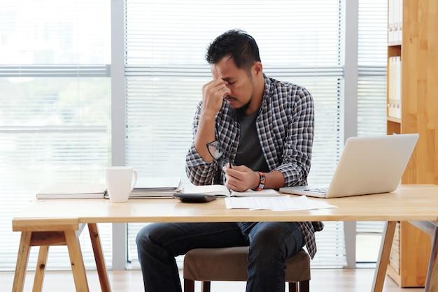 Betonter asiatischer mann, der bei tisch mit laptop und dokumenten sitzt und stirn reibt