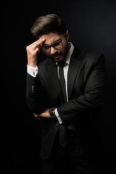 Betonter indischer geschäftsmann mit kopfschmerzen oder migräne. stehend auf schwarzem hintergrund isoliert trägt eine brille