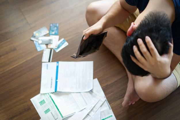 Betonter junger asiatischer mann, der leere geldbörse hält und an das finden des geldes denkt, um rechnungen zu zahlen.