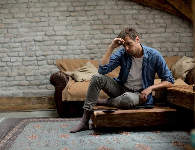 Betonter junger mann, der im raum sitzt