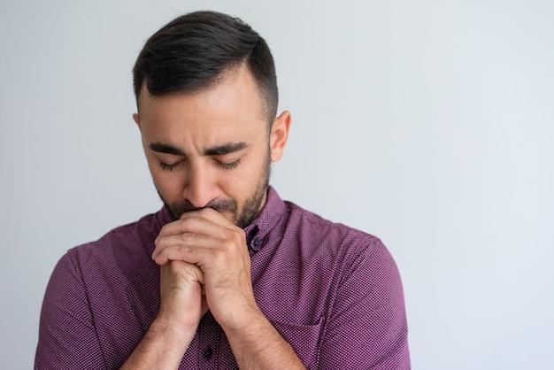 Betonter kerl, der schwierigkeiten sich fühlt und um hilfe betet