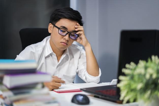Betonter mann, der mit buch und laptop studiert