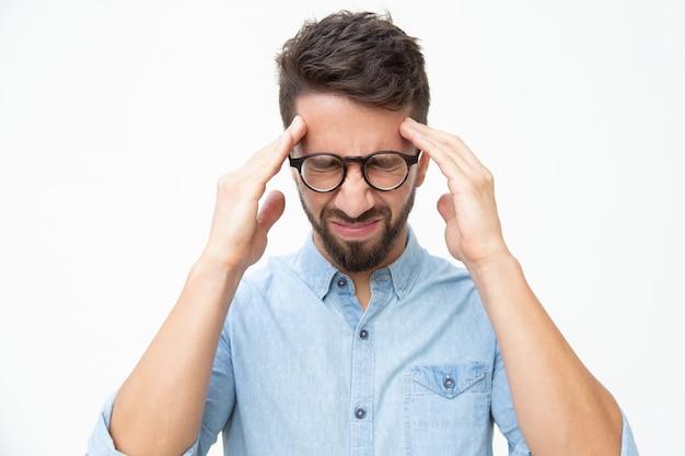 Betonter mann, der unter kopfschmerzen leidet